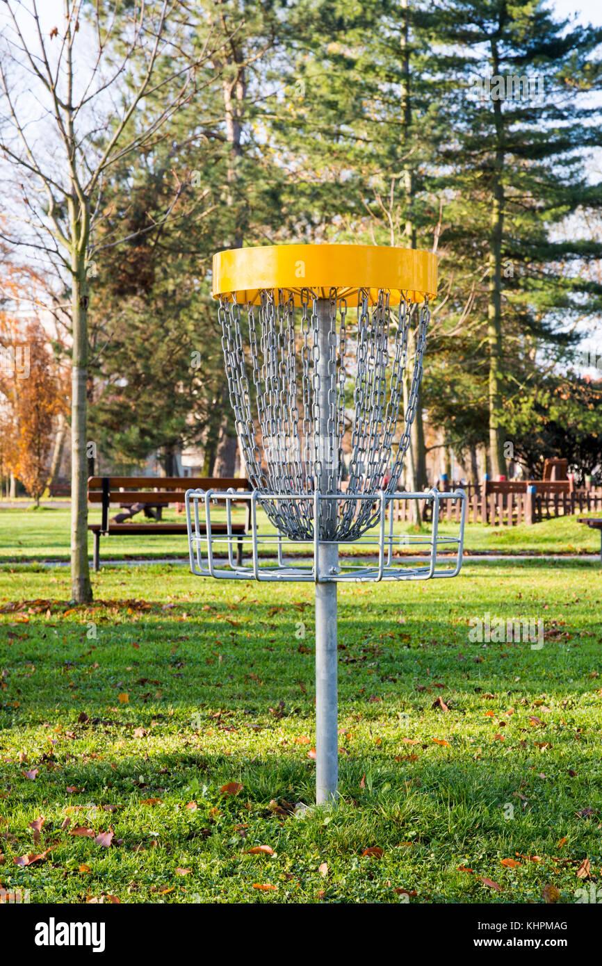 Giocando a basket con catene per gettare i dischi volanti nel parco con alberi secolari e di erba Foto Stock