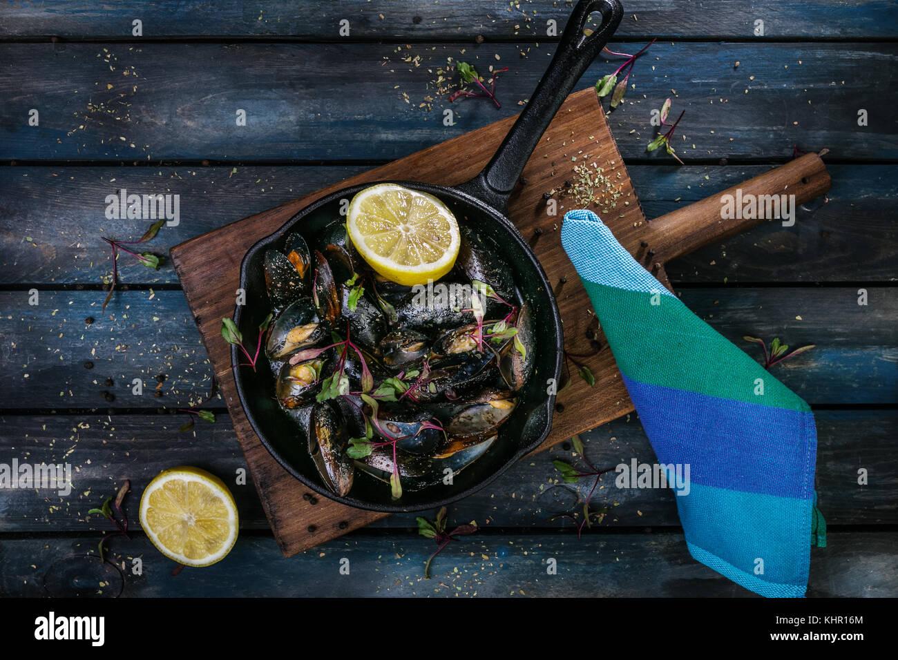 Deliziose le cozze. in servizio su una padella calda con erbe aromatiche spezie e limone su un colore di sfondo Immagini Stock