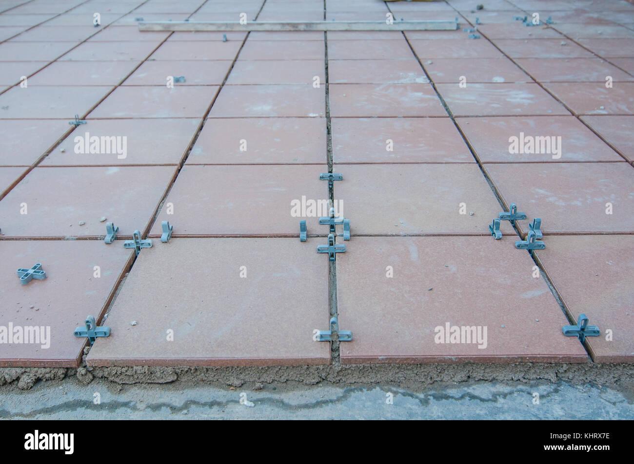 Installazione di piastrelle su un pavimento per terrazzo e alcuni