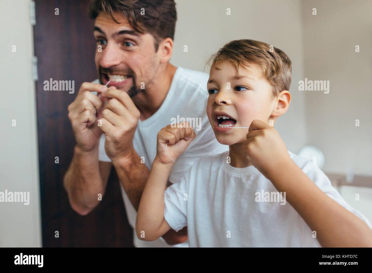 Bambino con il suo padre nel bagno pulire i denti con filo interdentale. Entrambi i cerchi in uno specchio e spazzolare Immagini Stock