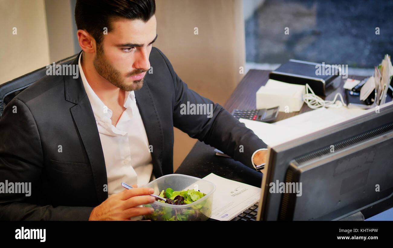 Ufficio Elegante Jobs : Uomo elegante in tuta avente il pranzo a tavola in ufficio mentre
