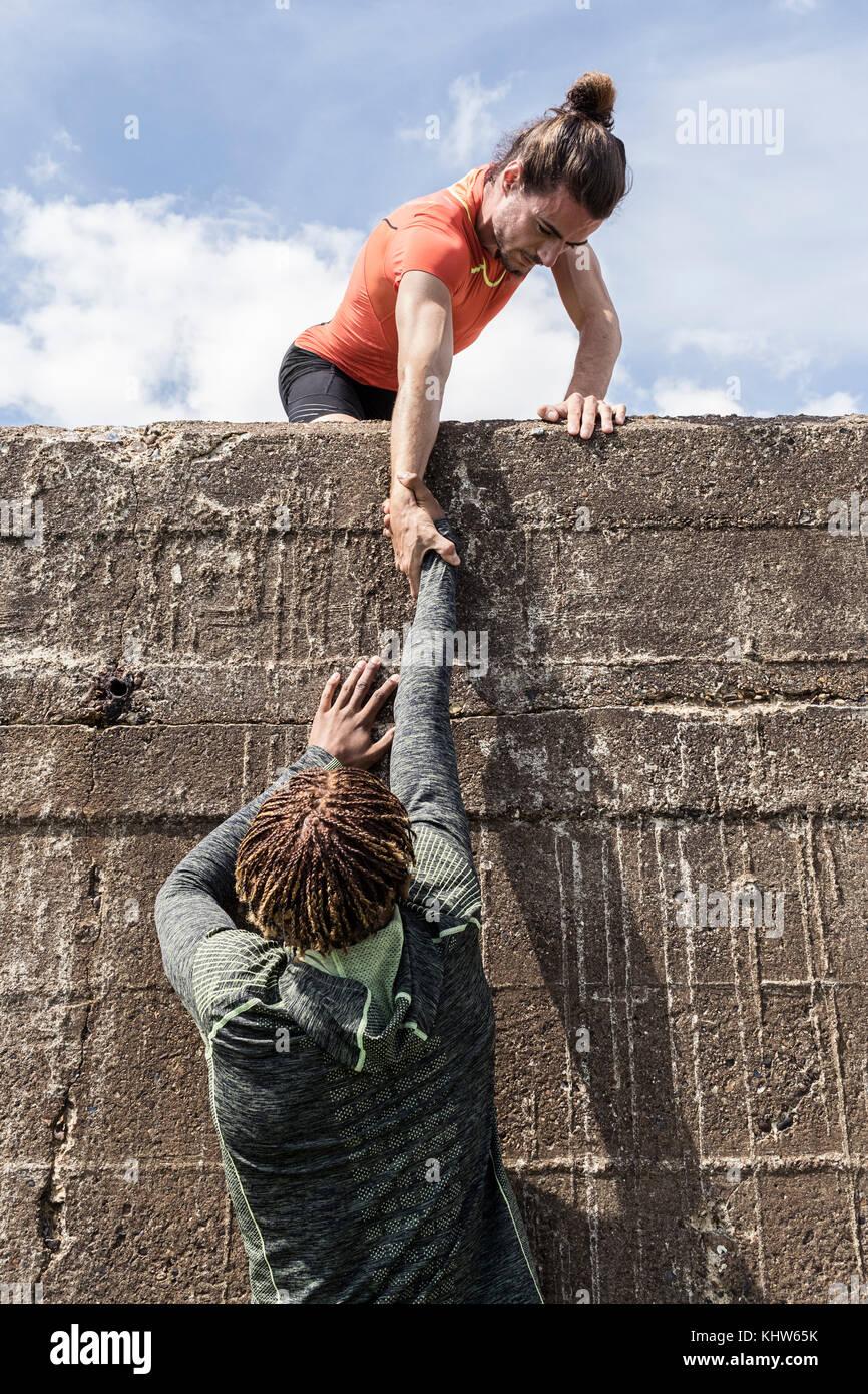 Giovane maschio free climber alla sommità della parete del mare aiutando un amico di salire Immagini Stock