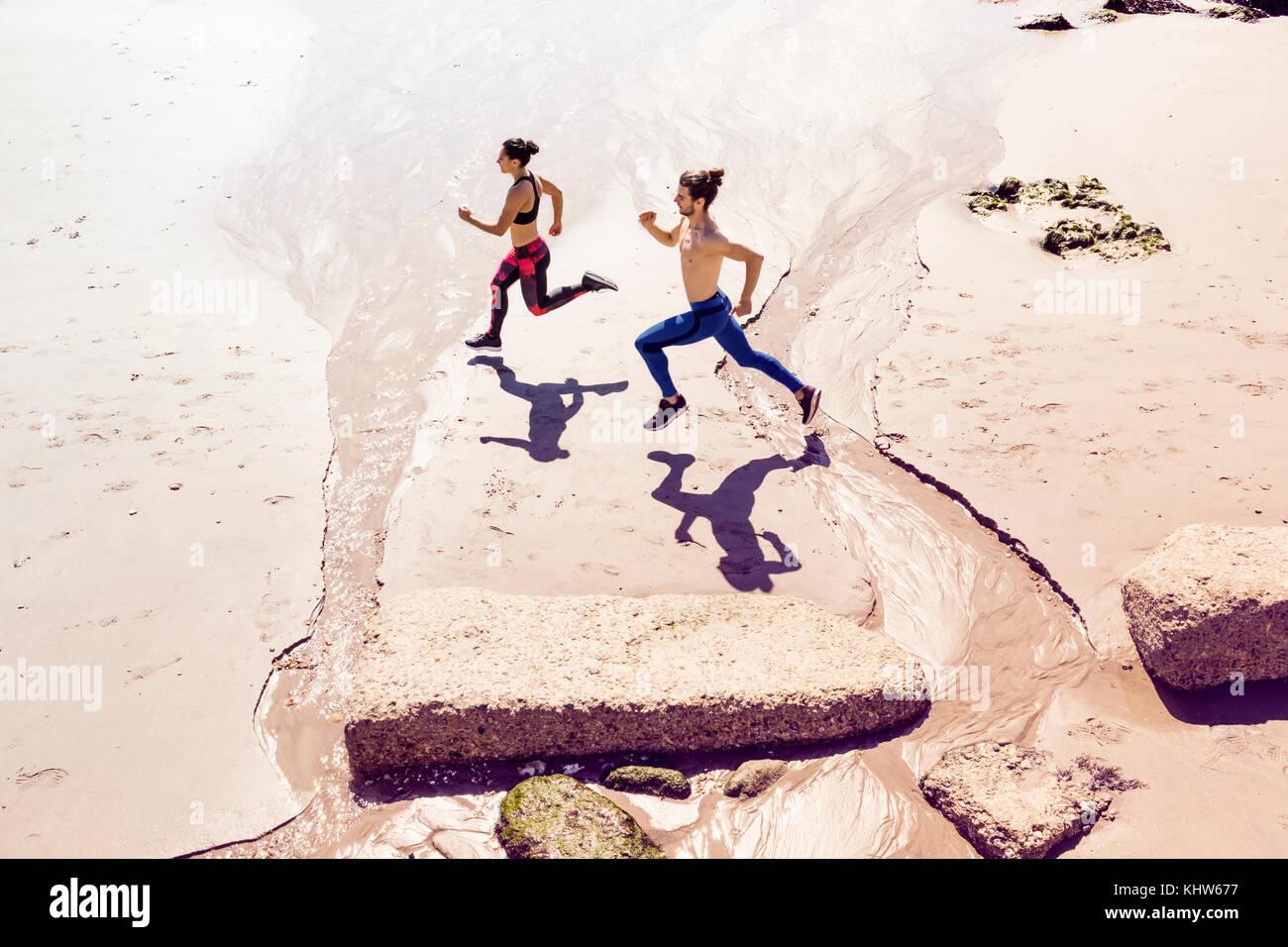 Giovane uomo e donna in corsa lungo la spiaggia, vista in elevazione Immagini Stock