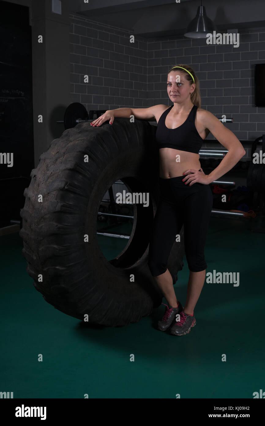 Donna bodybuilding fitness. donna in posa vicino al pneumatico in palestra Foto Stock