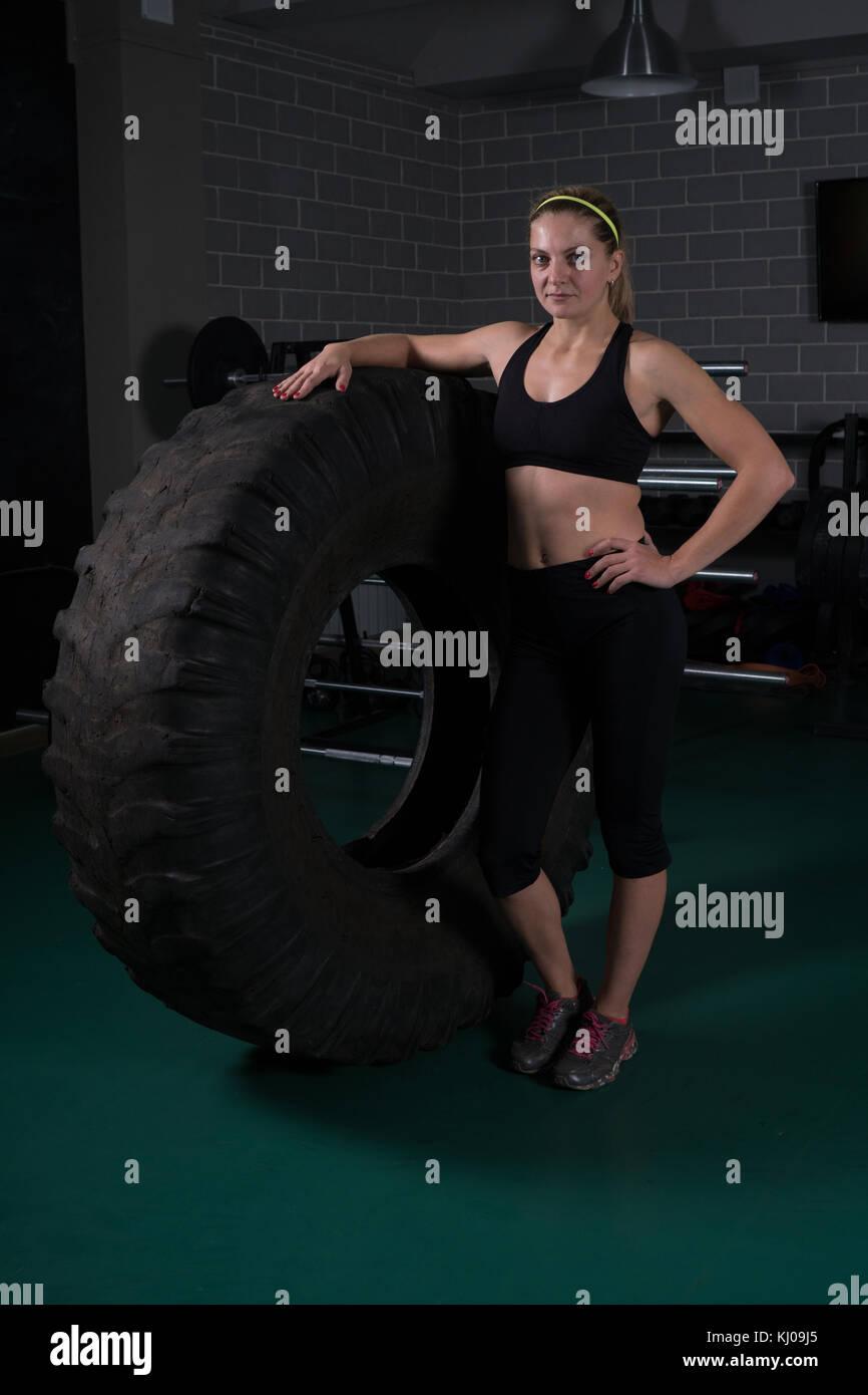 Donna bodybuilding fitness. donna in posa vicino al pneumatico in palestra Immagini Stock
