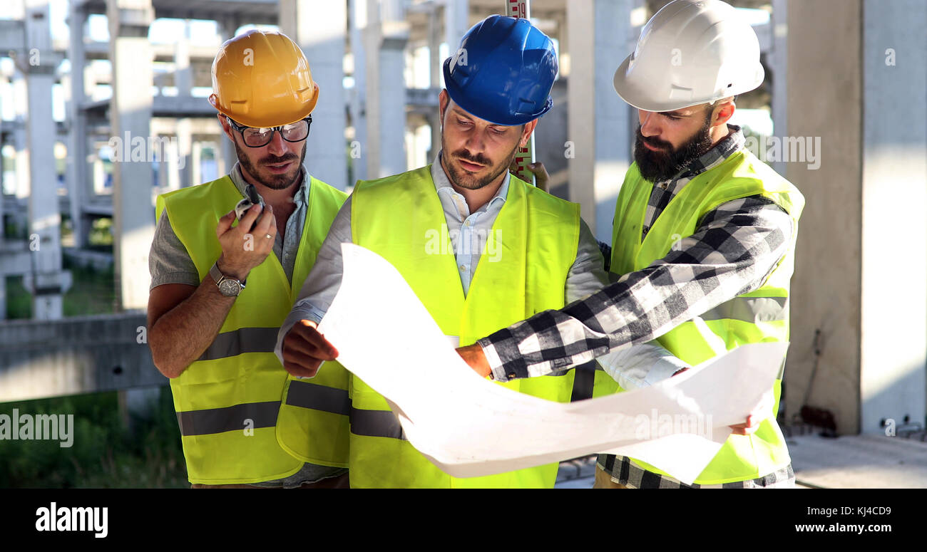 Costruzione Engineers discussione con gli architetti a sito in costruzione Foto Stock