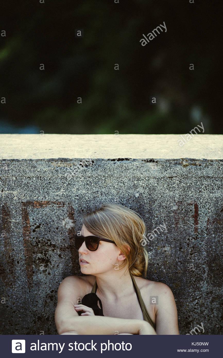 Giovane donna in occhiali da sole seduto da parete in calcestruzzo Immagini Stock