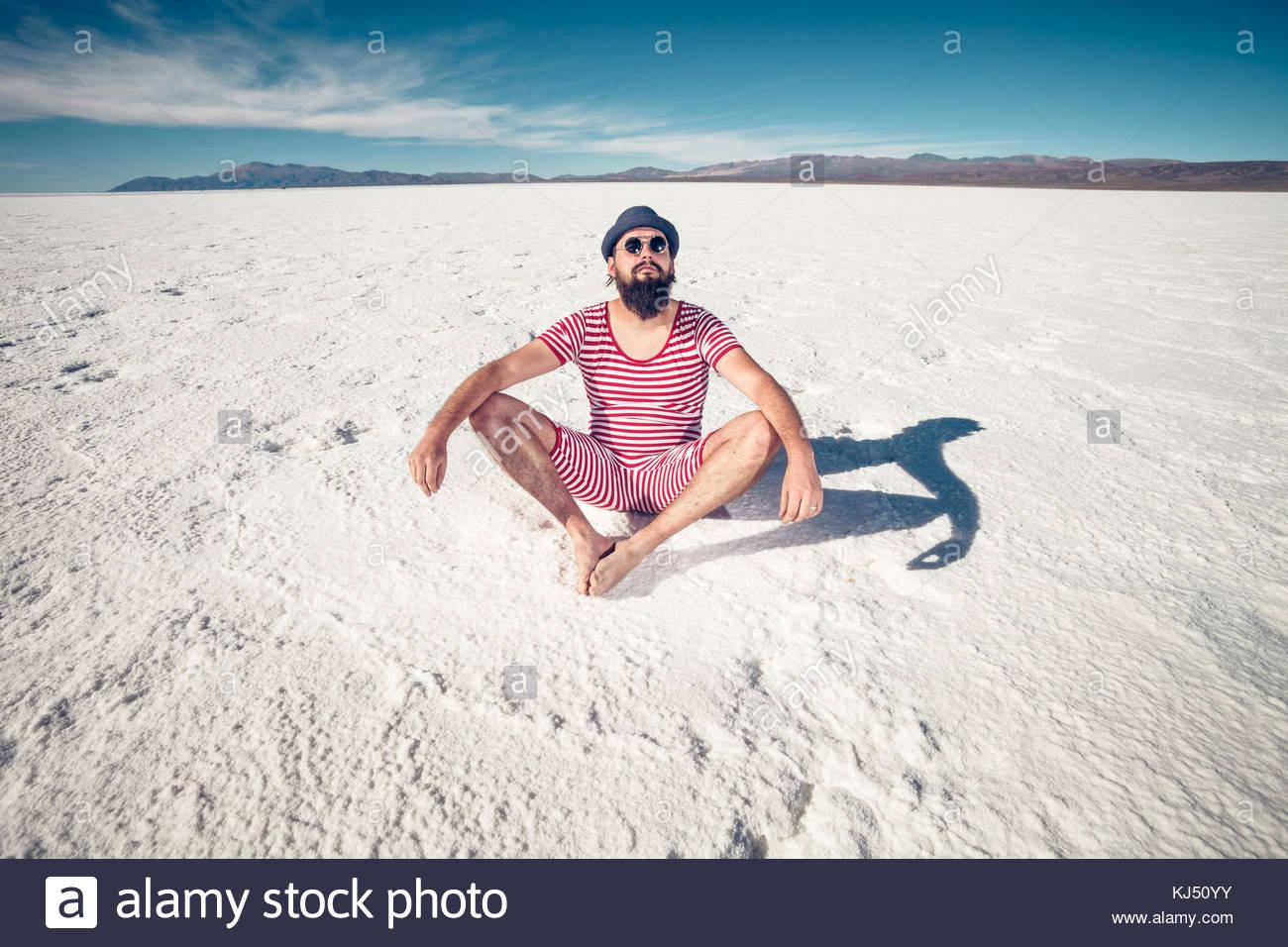 Eccentrico uomo meditare in un deserto bianco Immagini Stock