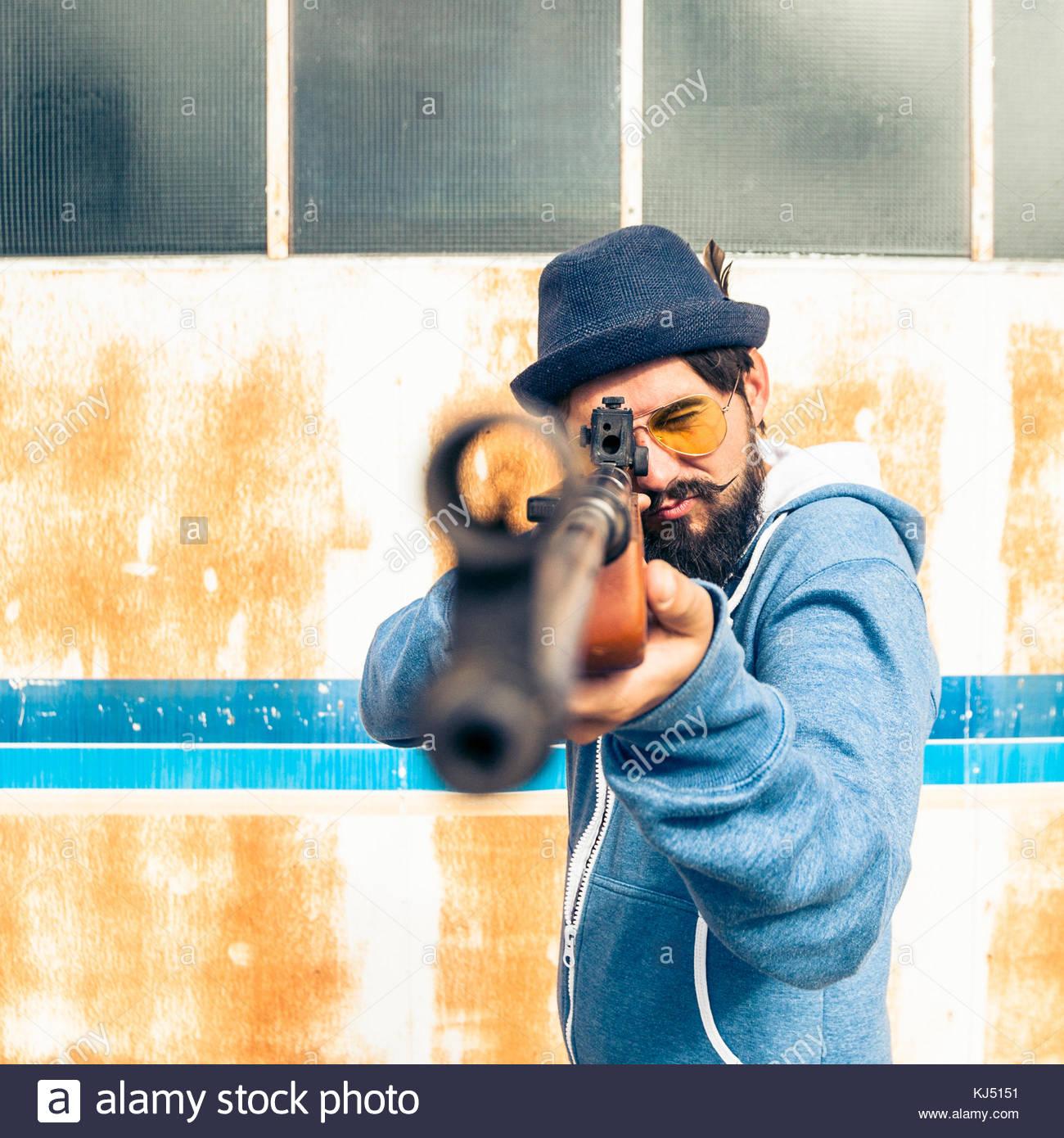 Un uomo indica il fucile da caccia a un bersaglio Immagini Stock