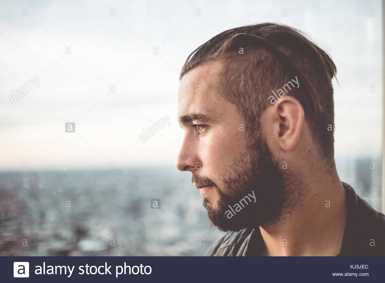 Uomo che guarda fuori dalla finestra Immagini Stock