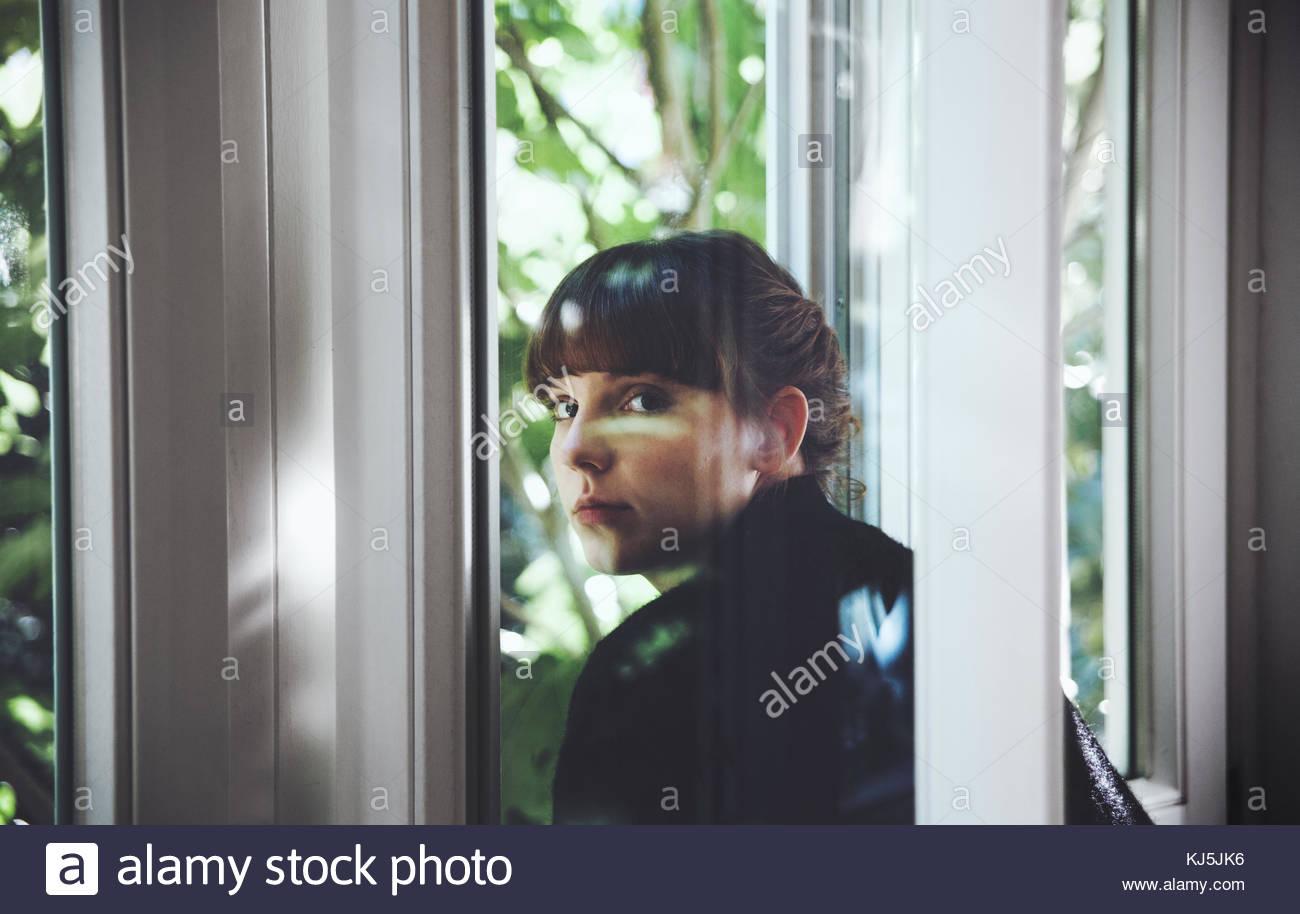 La donna dietro la finestra Immagini Stock