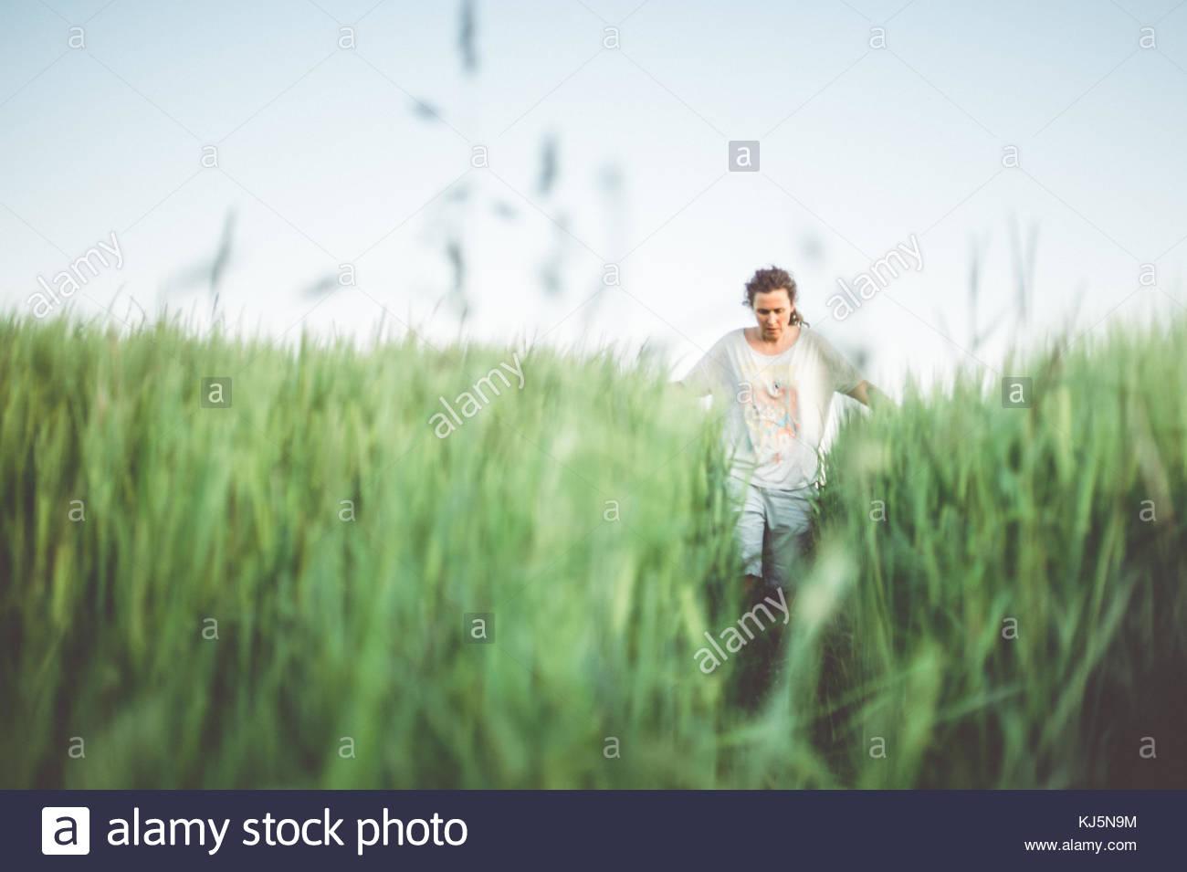 Uomo che cammina attraverso il campo verde Foto Stock