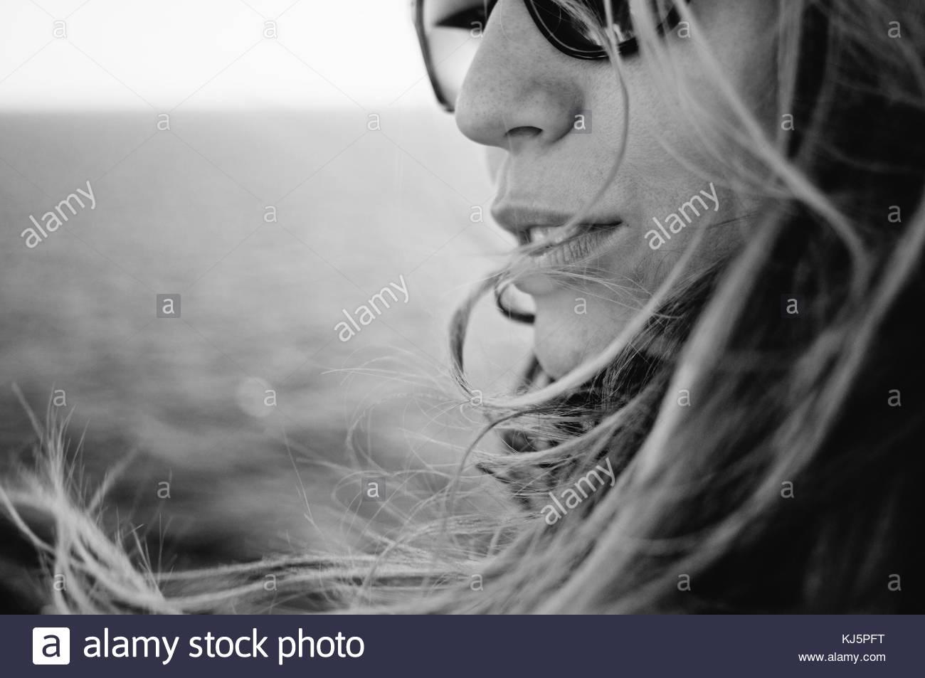 Donna sorridente con i capelli lunghi e occhiali da sole Immagini Stock