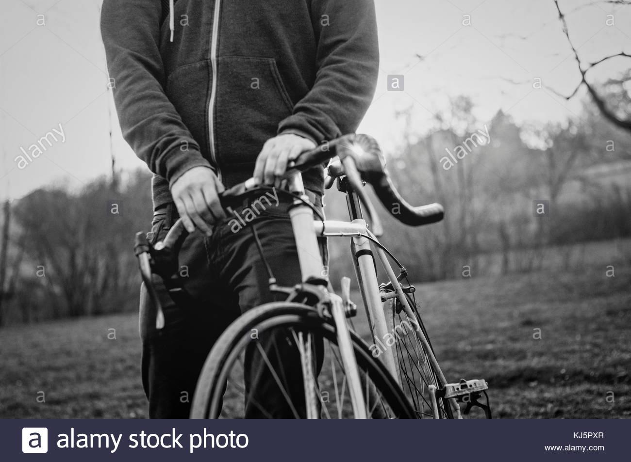 Uomo con una bicicletta su erba Immagini Stock