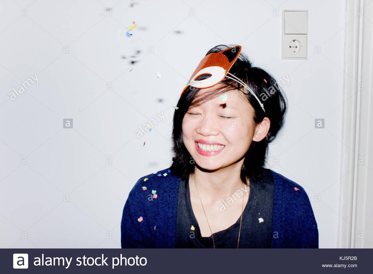 Donna sorridente con maschera di Fox e coriandoli Immagini Stock
