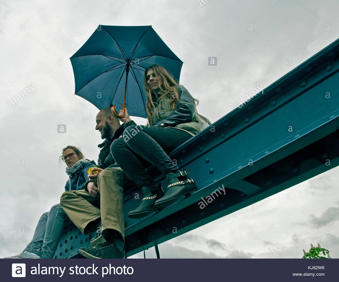 Tre amici seduti su una ringhiera a ponte in un giorno di pioggia. basso angolo di visione Immagini Stock