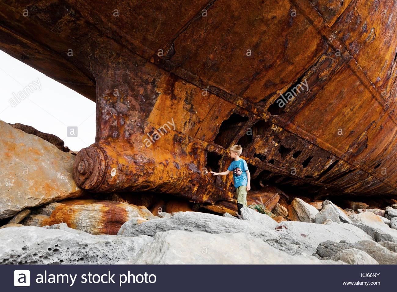 Ragazzo giovane toccare un relitto di una nave Immagini Stock