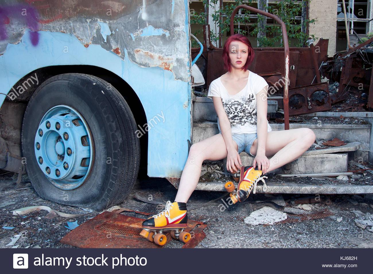 Redhead ragazza con i pattini a rotelle nel cantiere di demolizione Immagini Stock