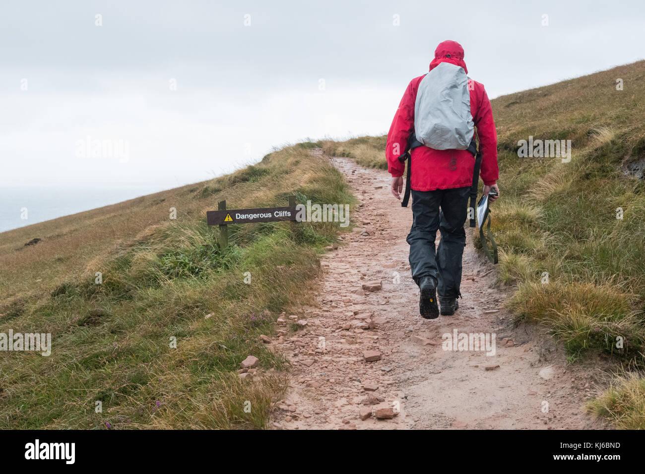 Uomo che cammina sul vecchio uomo di hoy sentiero nel vento e pioggia passando scogli pericolosi segno, hoy, isole Immagini Stock