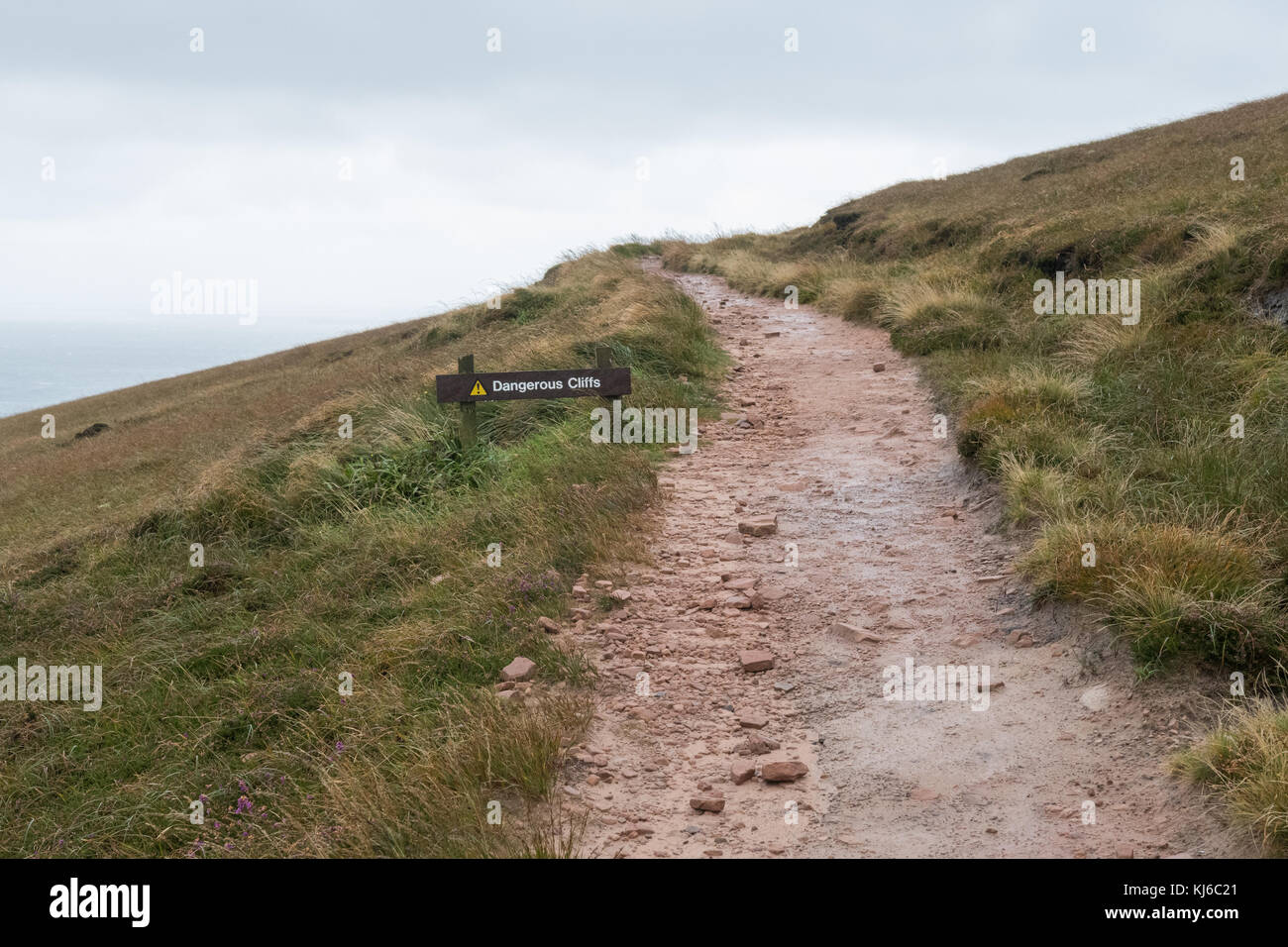 Scogli pericolosi segno accanto al sentiero scomparendo in lontananza, hoy, isole Orcadi Scozia, Regno Unito Immagini Stock