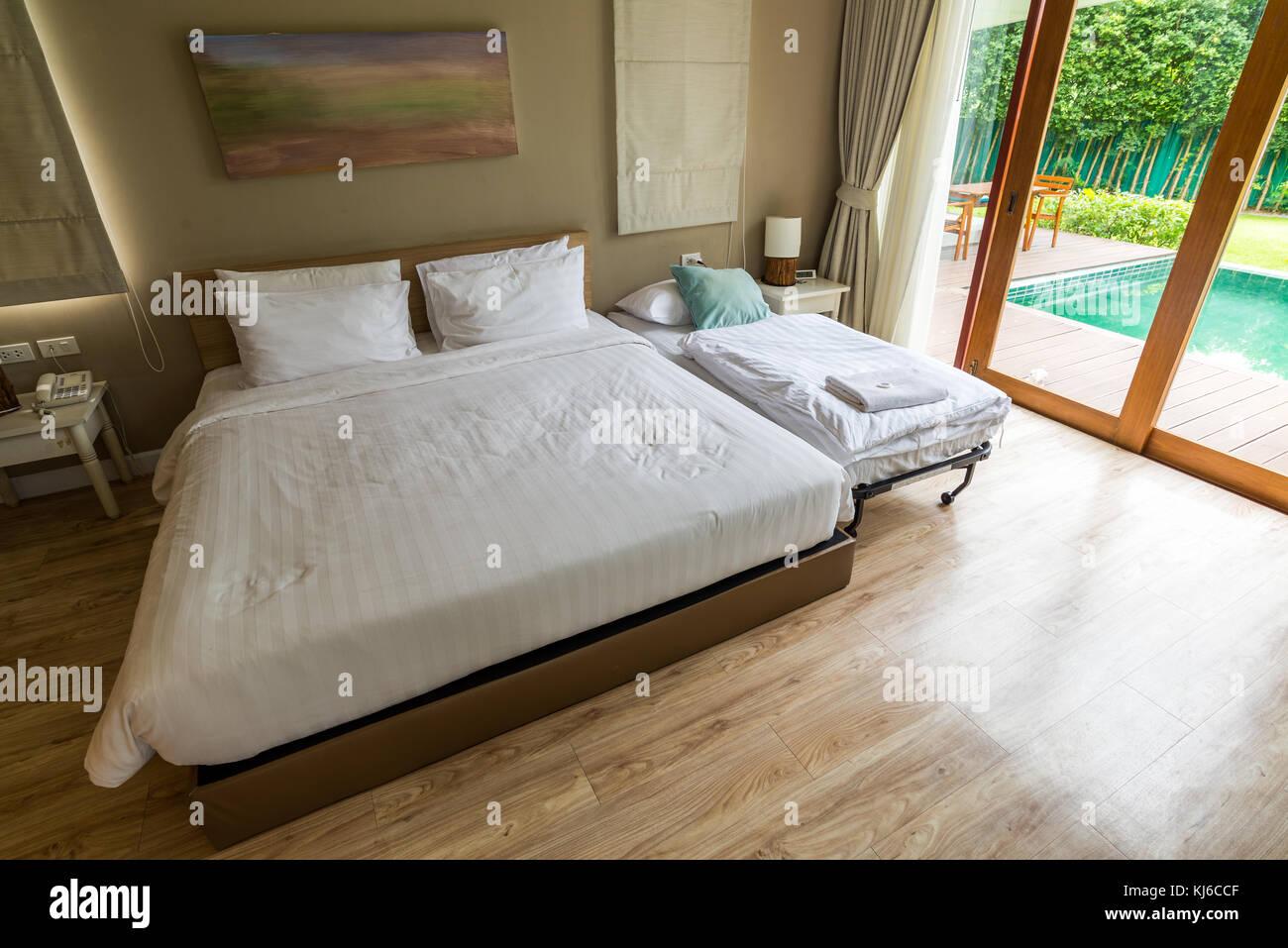 Bianca e moderna camera da letto sul pavimento di legno accanto alla ...