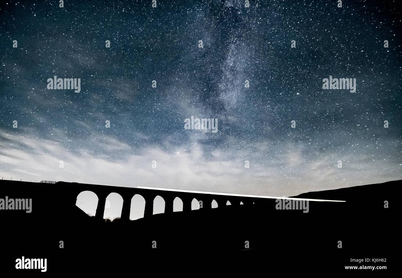 Una lunga esposizione di un treno che passa oltre il viadotto Ribblehead, mentre l'incredibile Via Lattea aumenta Immagini Stock