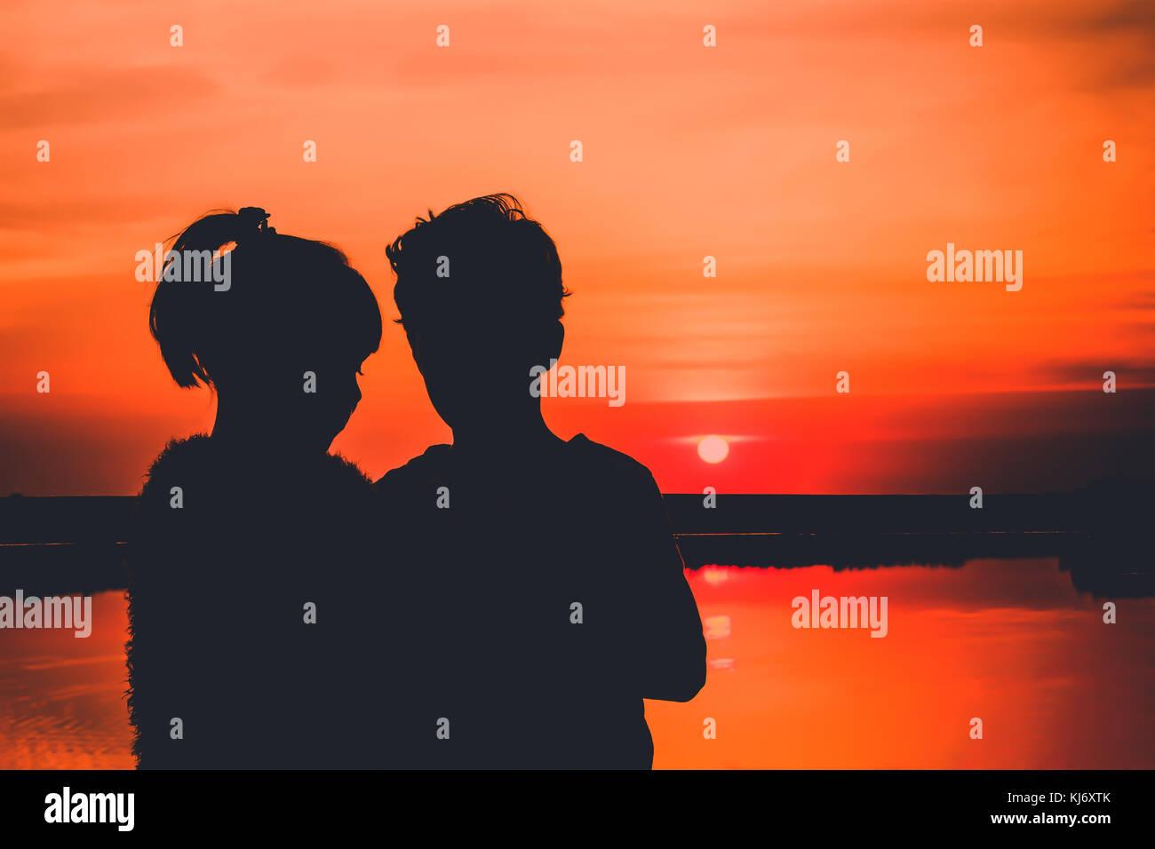 Coppia giovane in amore, sagome. piccolo ragazzo e ragazza si divertono, sullo sfondo vi è un bellissimo tramonto Immagini Stock