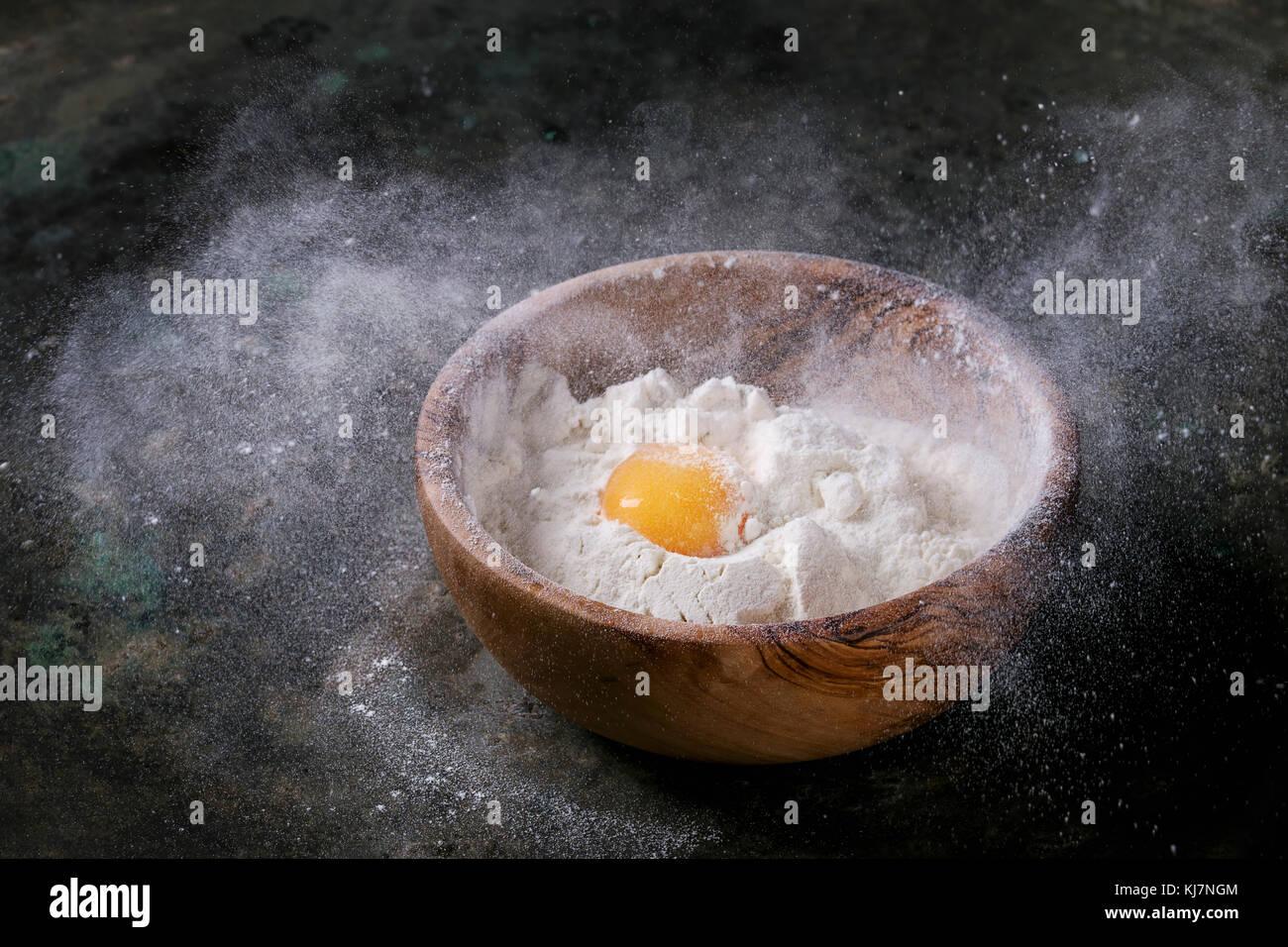 In legno di olivo ciotola con la farina di frumento e di tutto il tuorlo d'uovo su un vecchio metallo scuro Immagini Stock