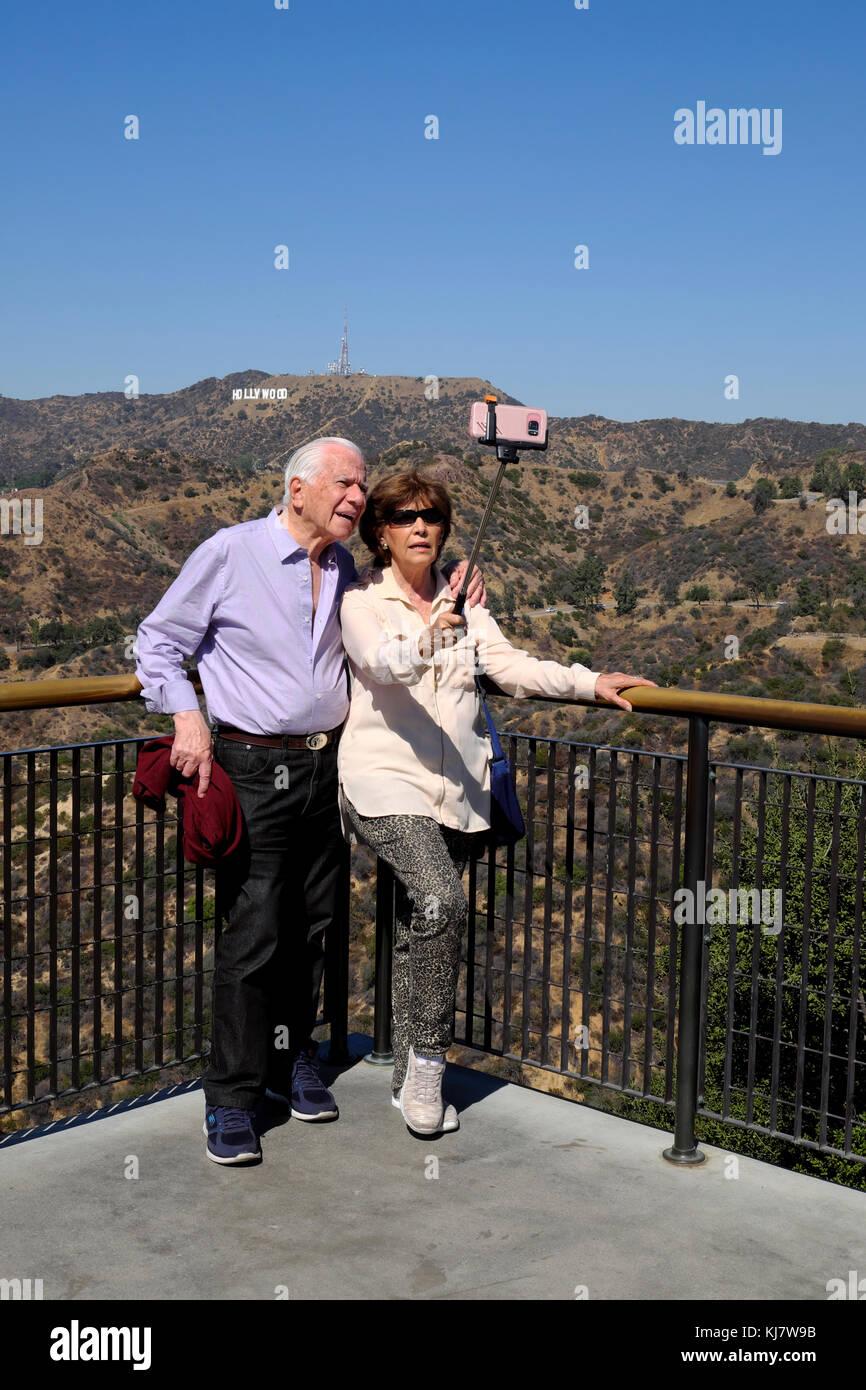 Coppia senior holding selfie stick tenendo cellulare foto di fronte di Hollywood Sign Parco Osservatorio Griffith Immagini Stock