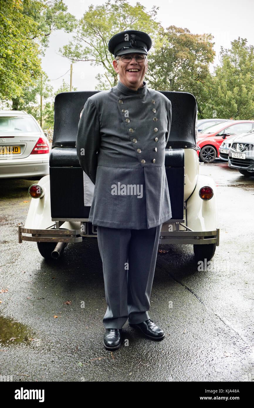 Un autista in uniforme nella parte anteriore del faux-auto d'epoca Immagini Stock