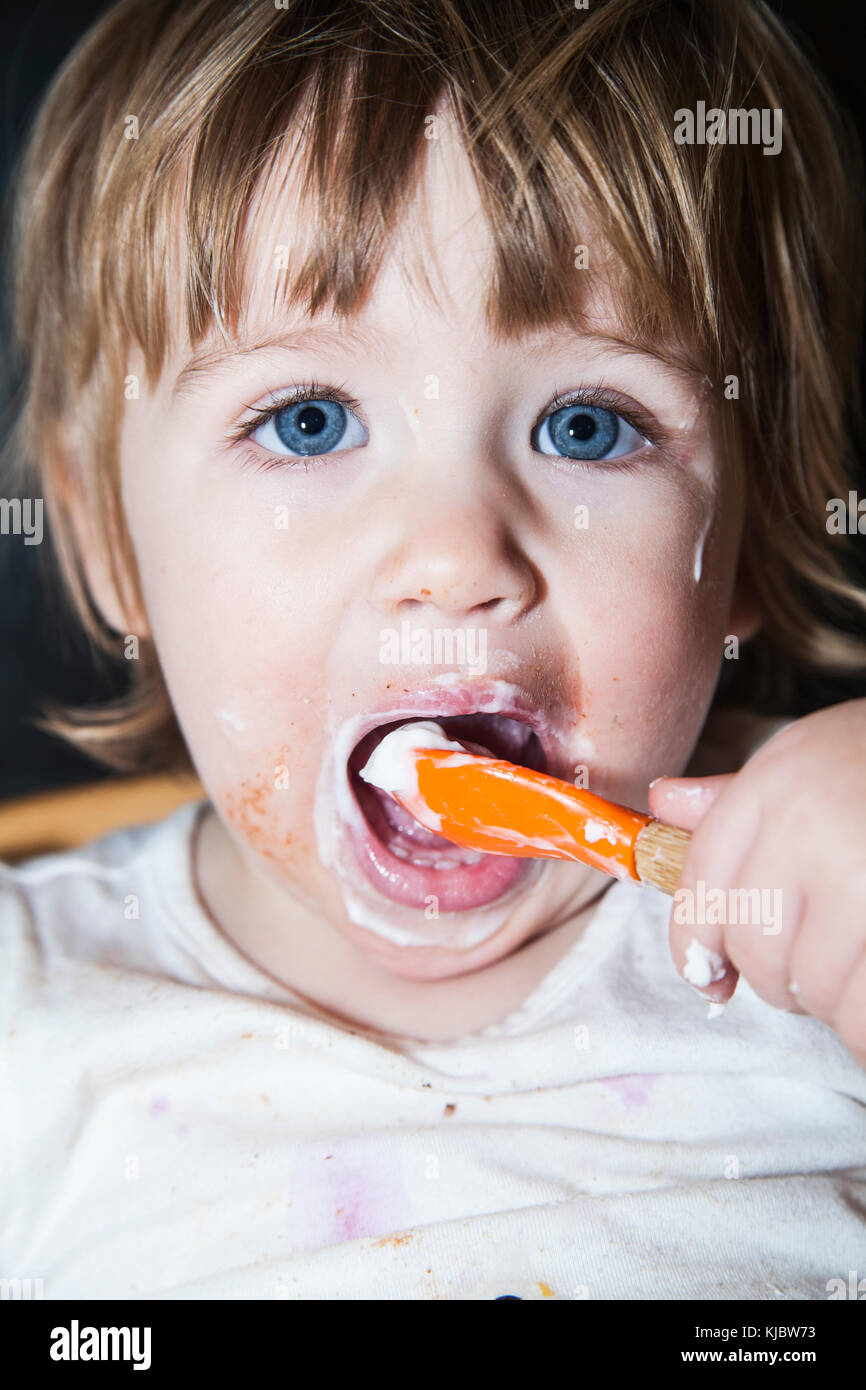 Confuso bambino mangiare con il cucchiaio Immagini Stock