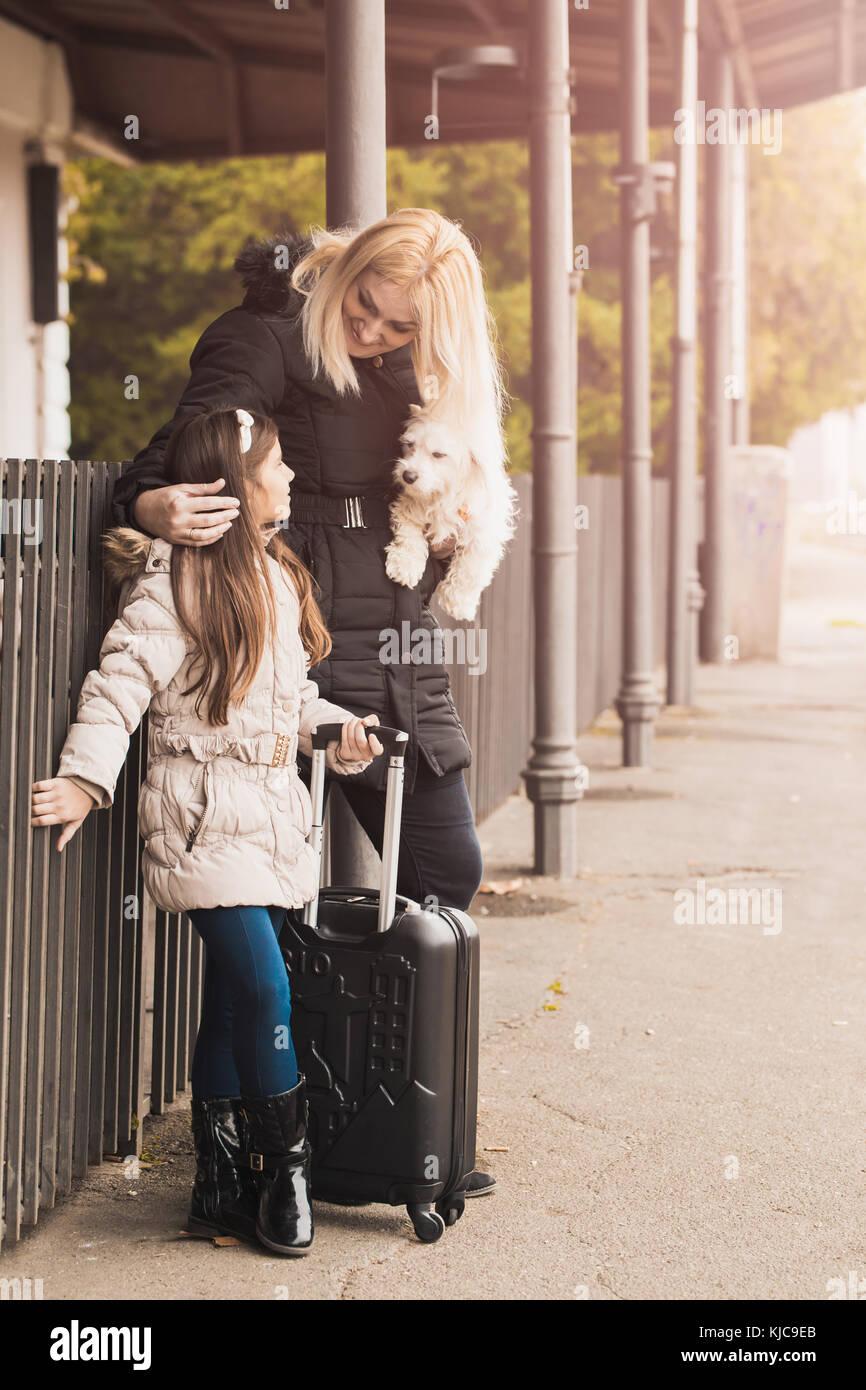 Madre e figlia ed il loro cane in una stazione ferroviaria. kid e la donna in attesa del treno e felici per un viaggio. Immagini Stock