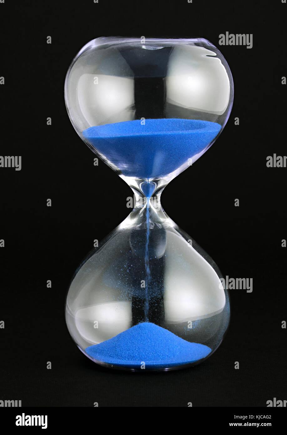 Close-up studio shot di una clessidra trasparente con sabbia blu versando come concetto di tempo e di conto alla Immagini Stock