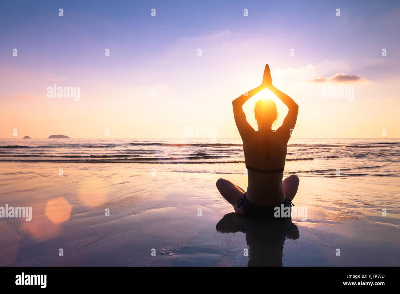 Lo yoga e la meditazione sulla calma tranquilla spiaggia al tramonto, montare la giovane donna Immagini Stock