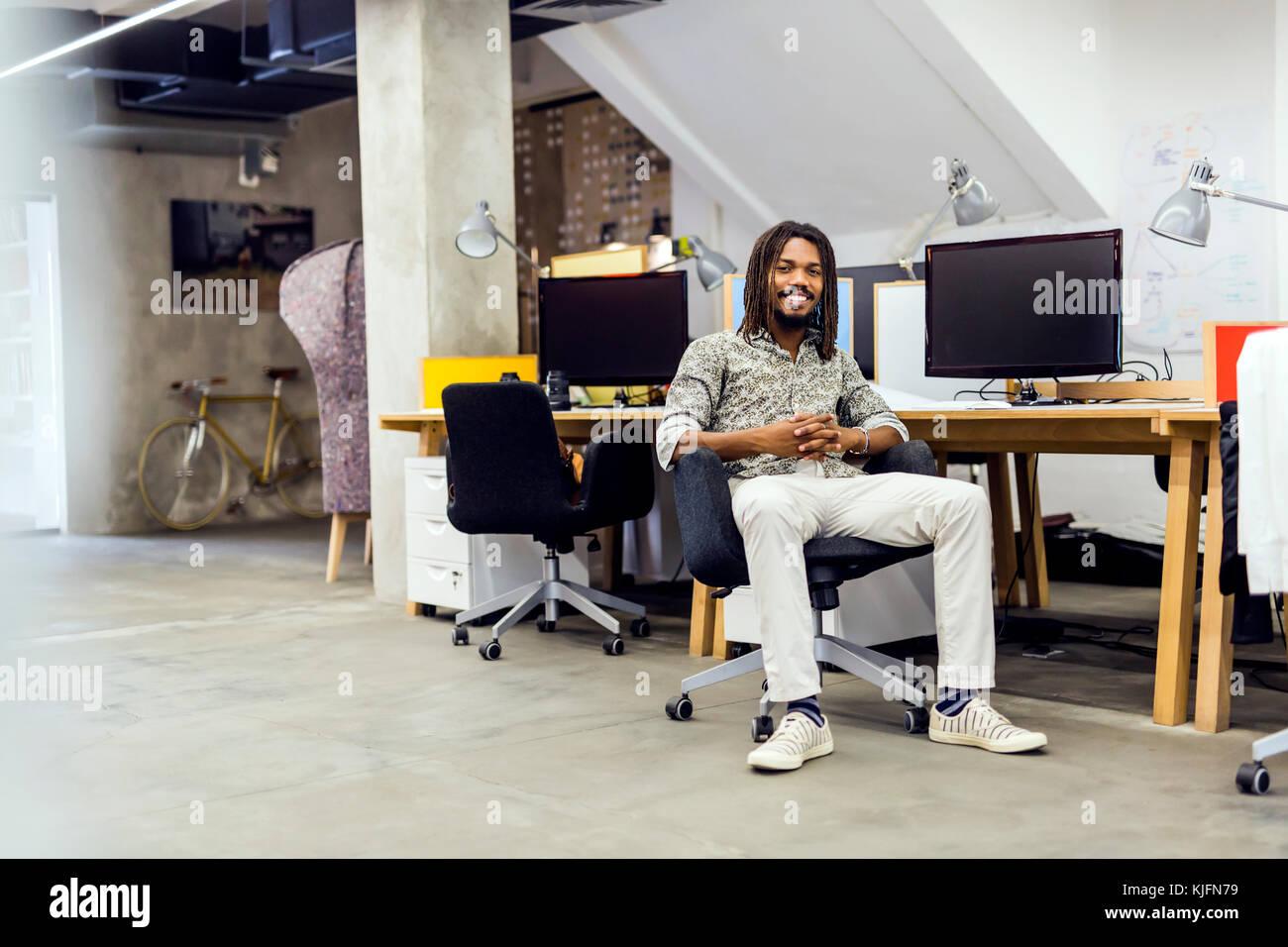 Bello graphics designer seduti ad una scrivania Foto Stock