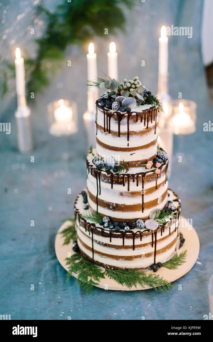 Il dessert, confezione, celebrazione concetto. tre tier bianco torta di nozze riccamente decorata con bacche e foglie, Immagini Stock
