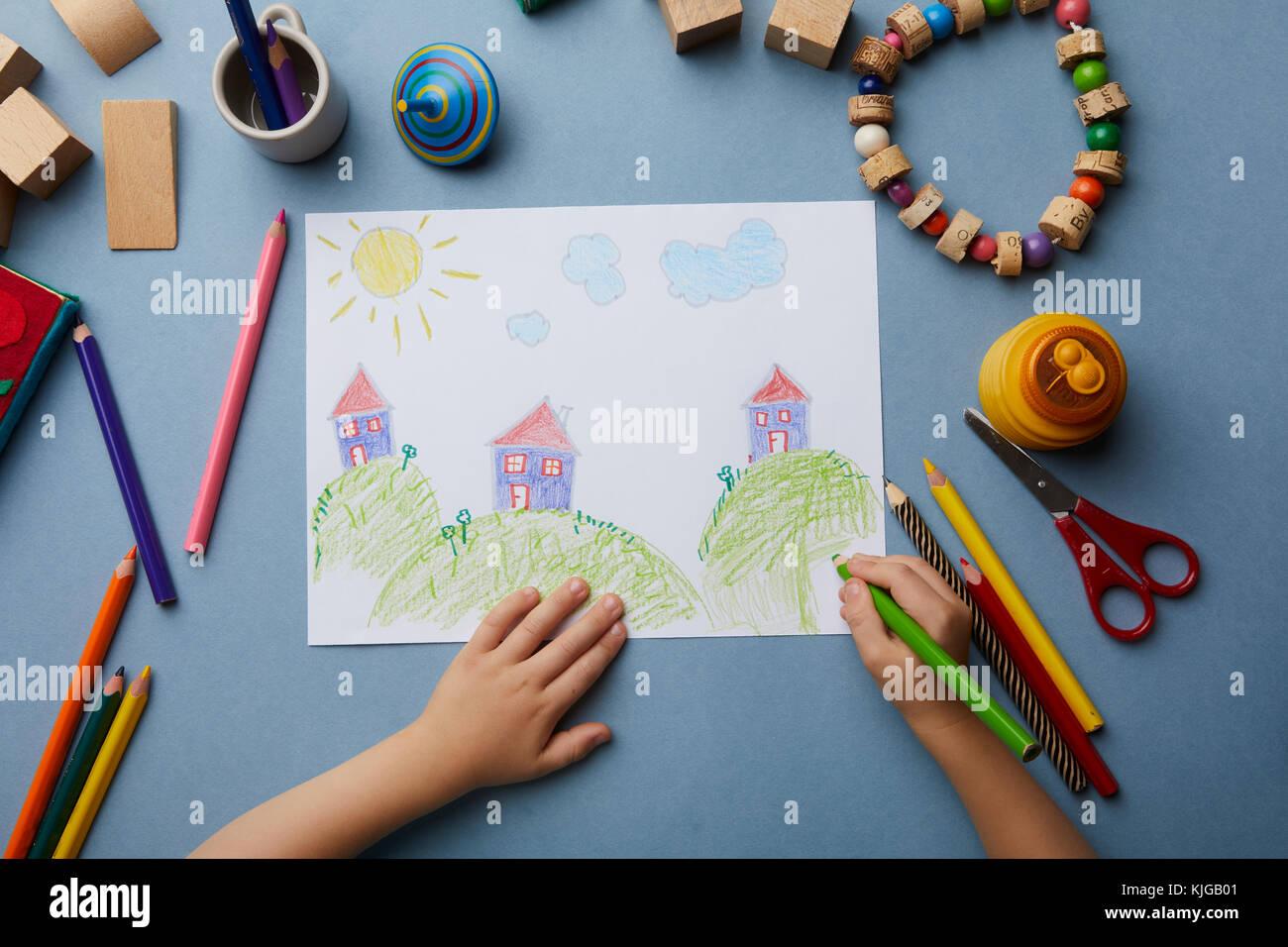 Bambino disegna il paesaggio con le case Immagini Stock