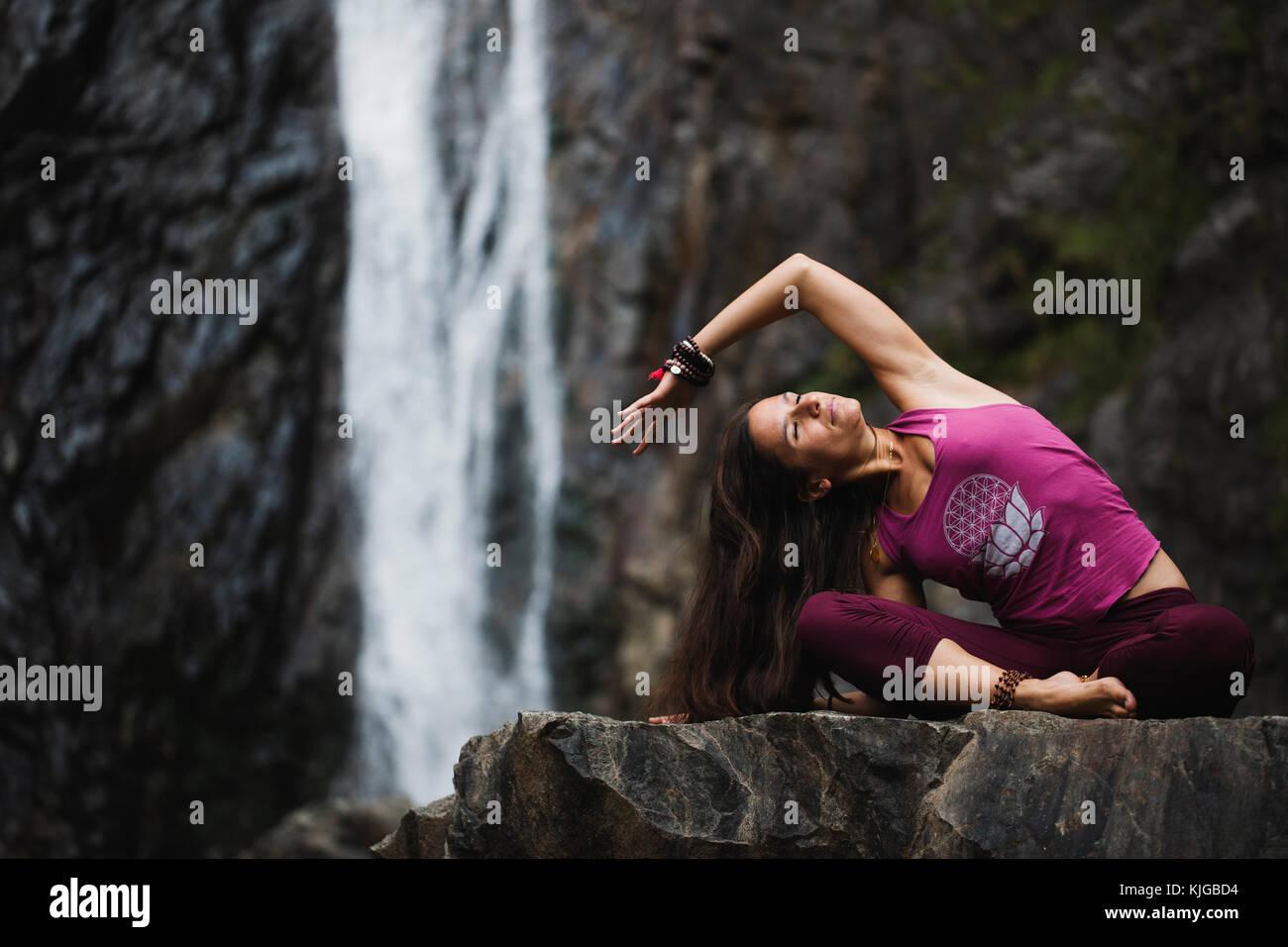 L'Italia, Lecco, donna facendo yoga pratica nei pressi di una cascata Immagini Stock