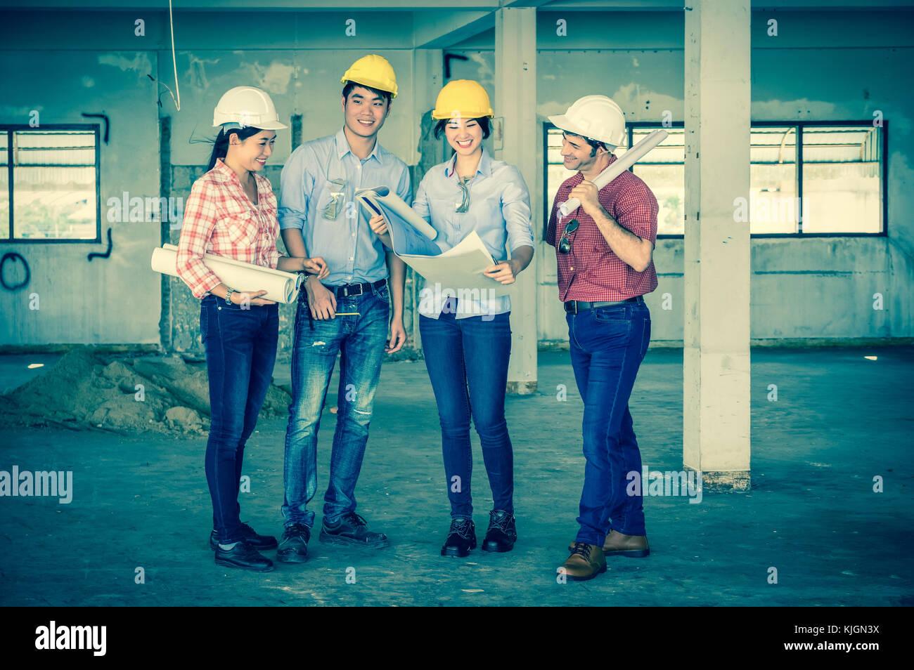 Multietnica costruzione professionale di ingegneri che lavorano con colleghi aziendale il lavoro di squadra e blueprint Immagini Stock