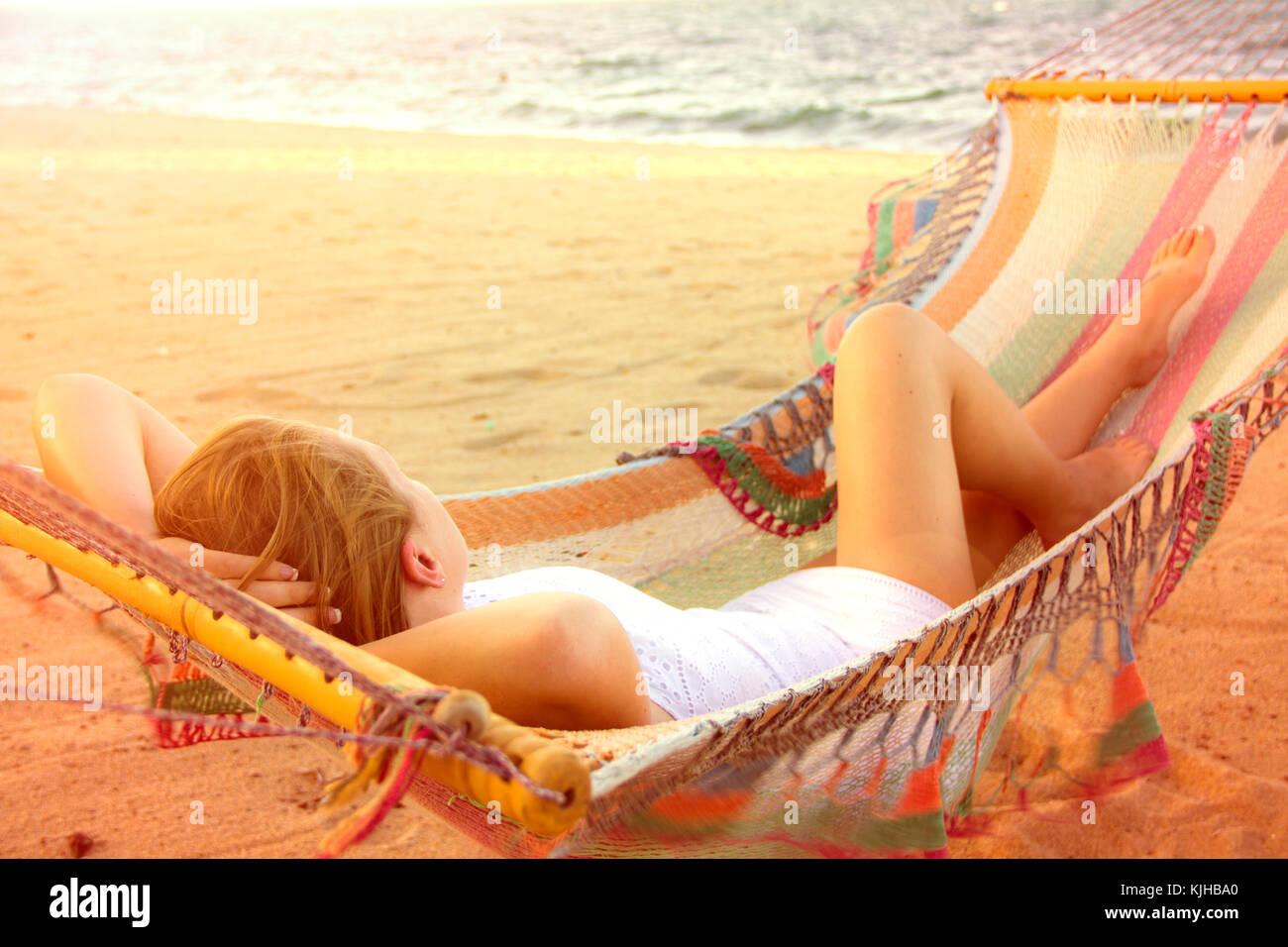 Bella ragazza in un abito bianco in un'amaca sulla spiaggia, beatamente in ammollo il luminoso sole estivo. Immagini Stock