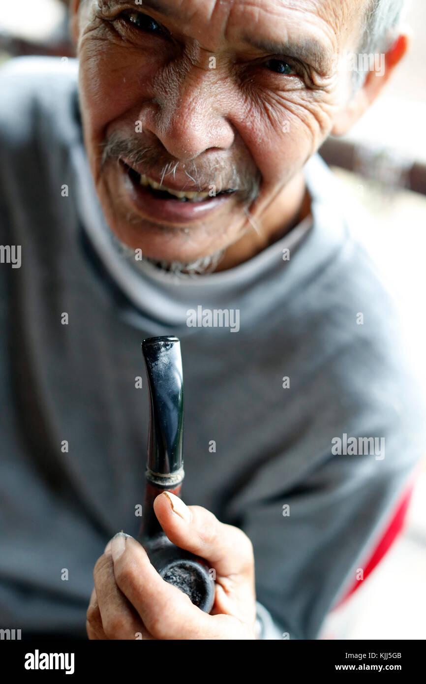 Bahnar (Ba Na) gruppo etnico. Ritratto di vecchio tubo smocking. Kon Tum. Il Vietnam. Immagini Stock
