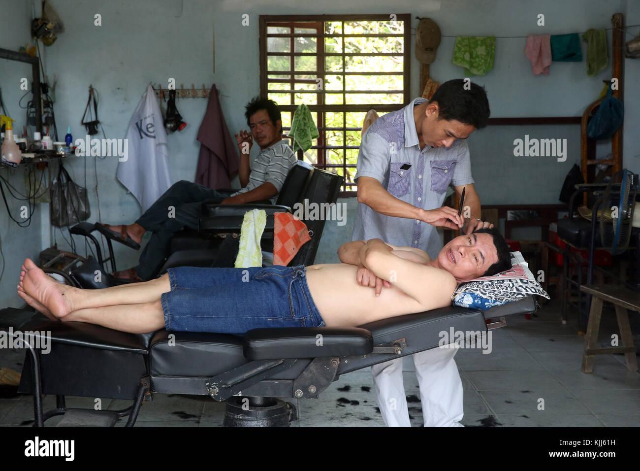 Parrucchiere. Barbiere cliente di rasatura. Hoi An. Il Vietnam. Immagini Stock