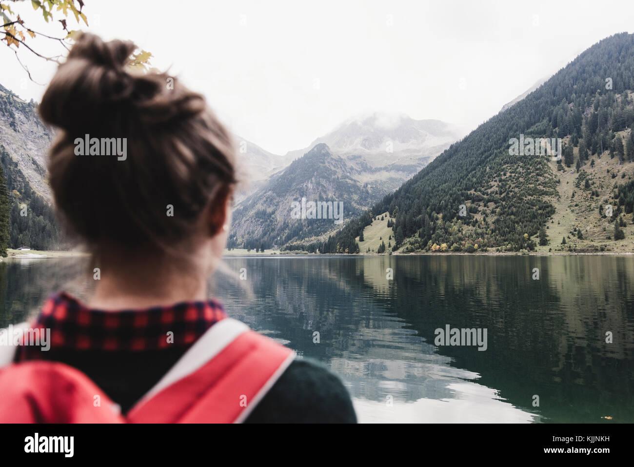 Austria, Tirolo, Alpi, vista posteriore di un escursionista al lago di montagna Immagini Stock