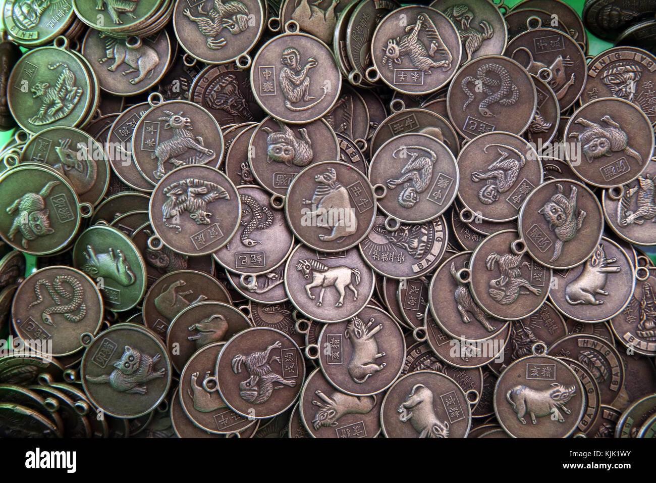 Dettaglio del economici buddista in miniatura di amuleti in cesti a fornitori stallo. Zodiaco Cinese: 12 segni di Immagini Stock