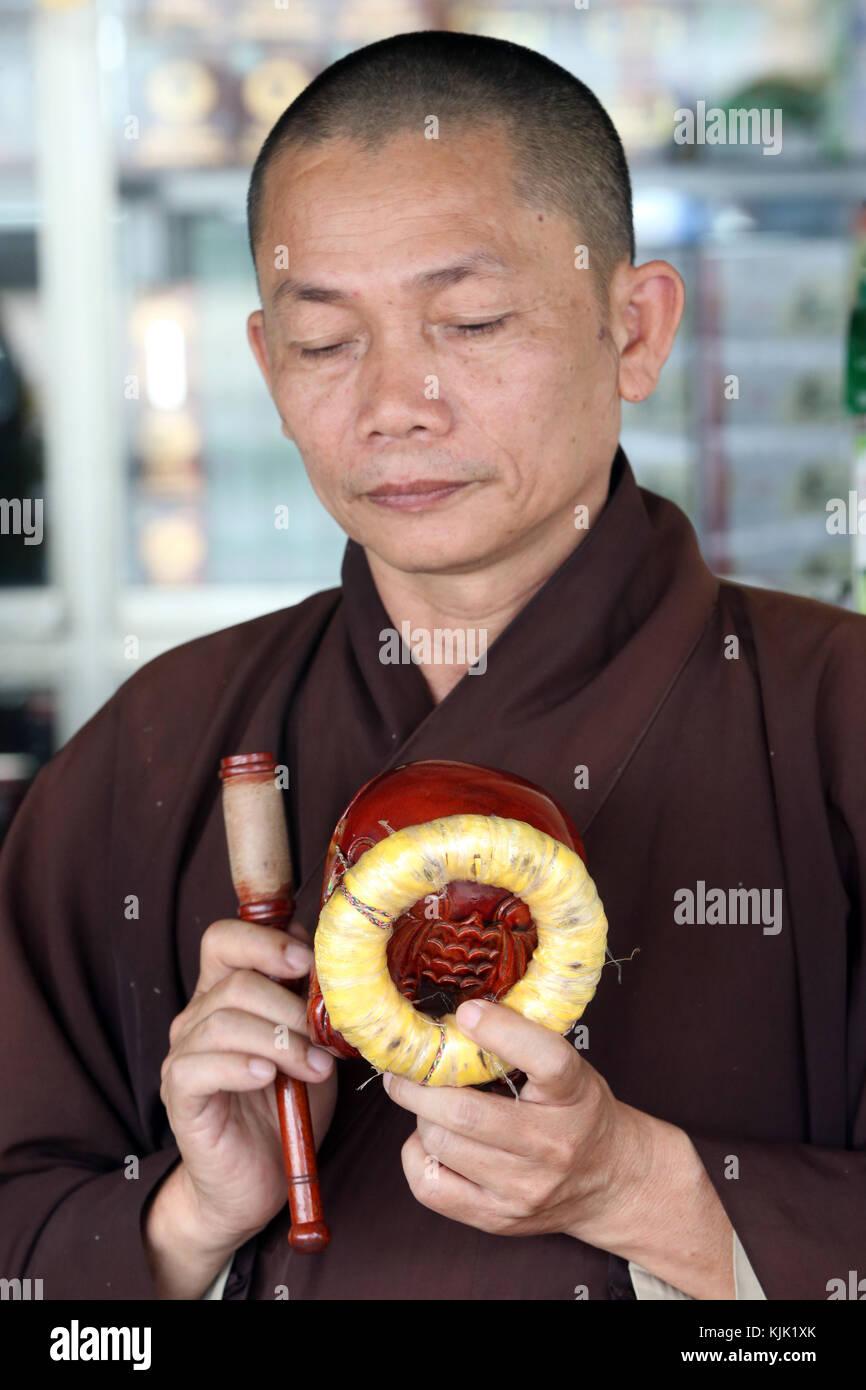 Cerimonia buddista. Monaco giocando su un pesce di legno (strumento a percussione). Danang. Il Vietnam. Immagini Stock