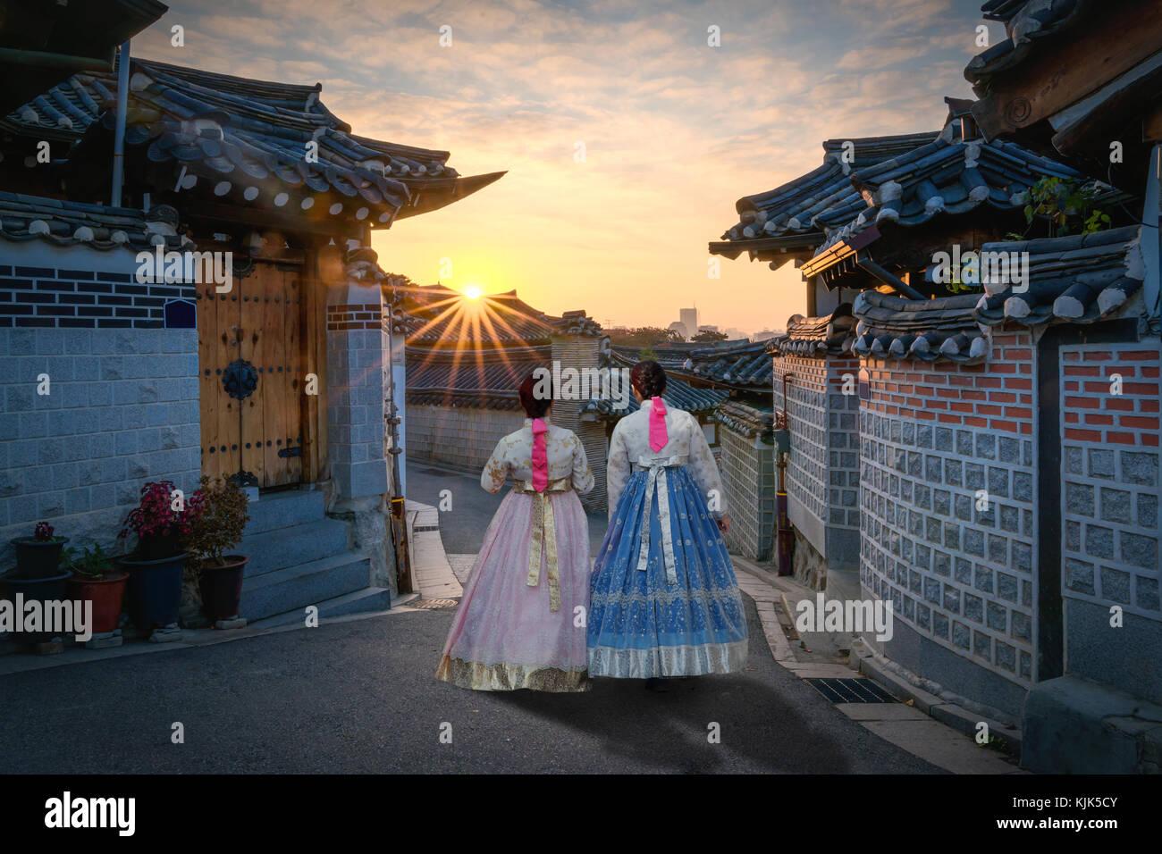 Indietro di due donne che indossano hanbok camminando attraverso lo stile tradizionale delle case di il villaggio Immagini Stock
