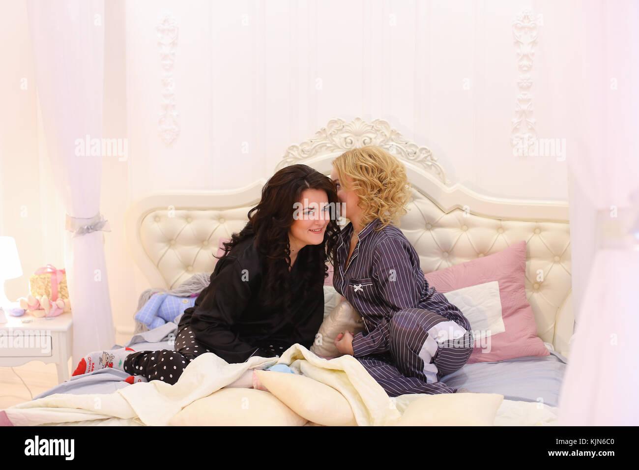Due amiche di chat e pettegolezzi seduta sul letto in bright