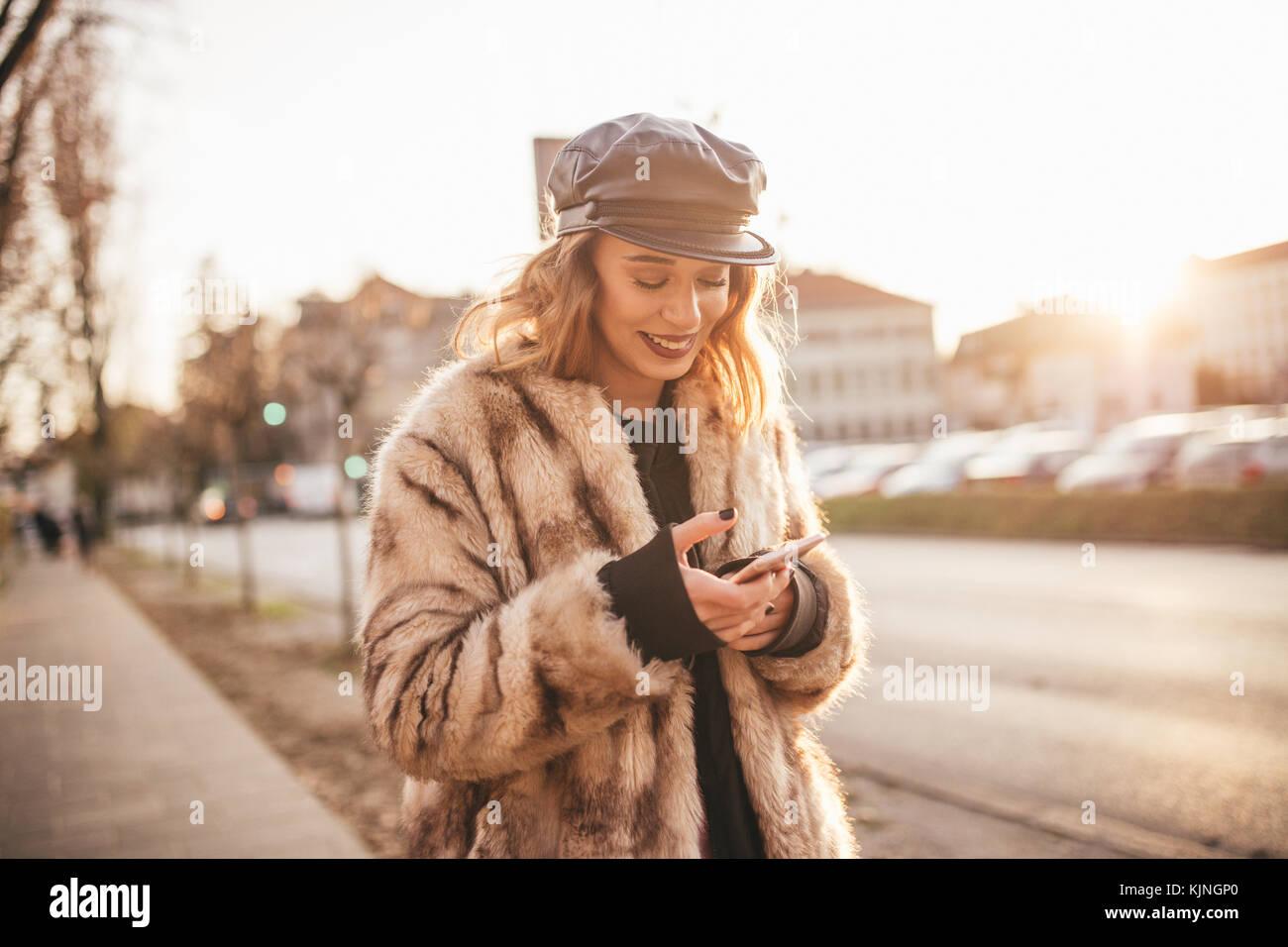 Bella ragazza sorridente e i messaggi di testo sul suo telefono cellulare sulle strade della città Immagini Stock