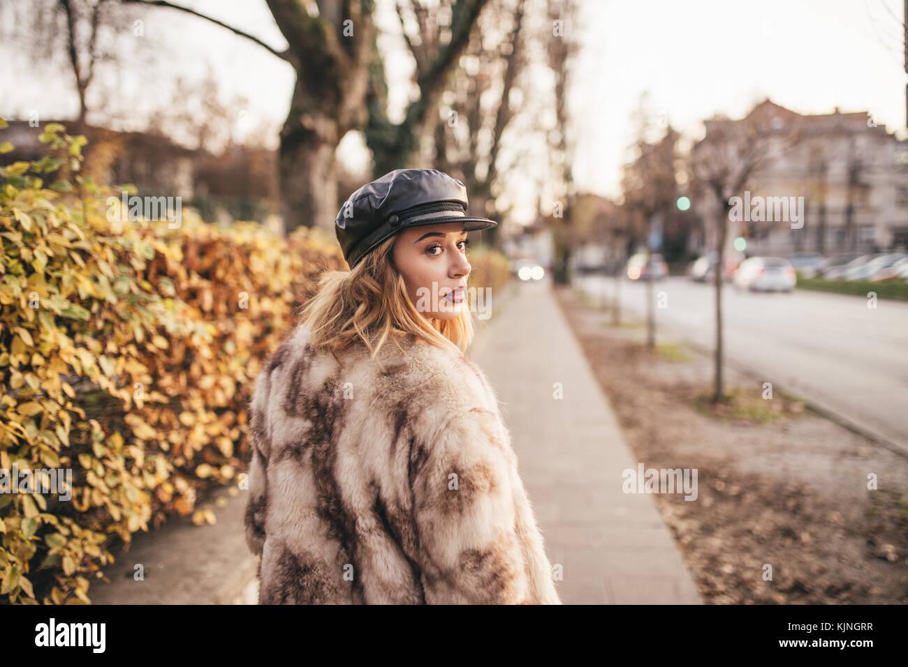 Bella ragazza che indossa la pelliccia e cavalcare la sua bicicletta sulle strade della città Immagini Stock