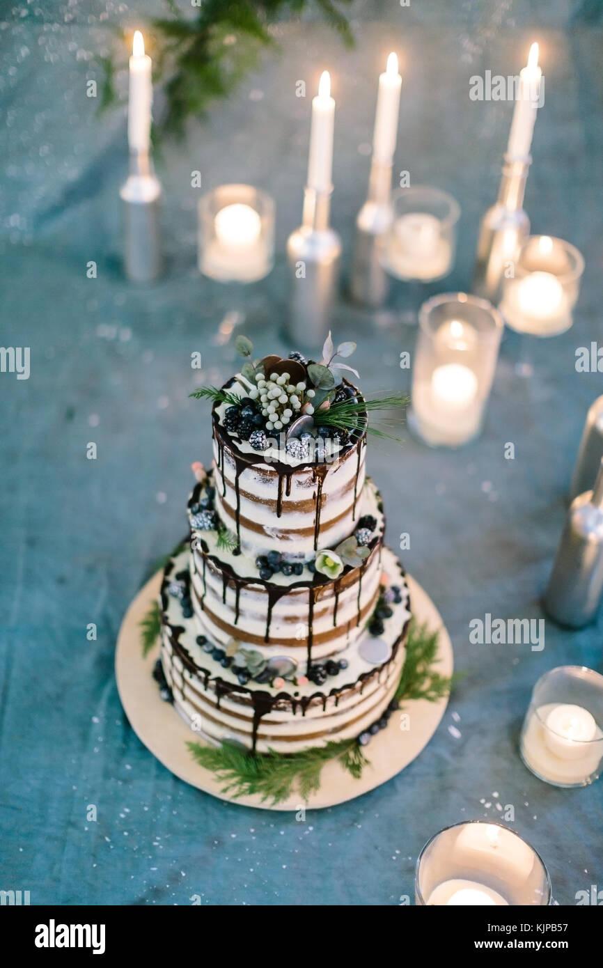 Trattamento, vacanze, dolciumi concetto. gteat tre tier torta di compleanno con foglie e fiori, con frutti di bosco Immagini Stock
